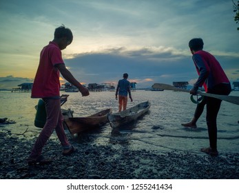 Sabah, Malaysia-Dec 01, 2018:Unidentified sea gypsy people handling their traditional canoe before going home to the stilt house during sunset in Sipadan Bodgaya island, Sabah, Malaysia.