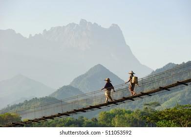 Die Dorfbewohner von Sabahan gehen durch eine Hängebrücke mit wunderschönem majestätischen Kinabalu auf dem Hintergrund.