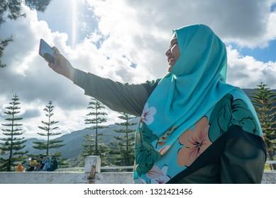 Sabah,Malaysia - 05-01-2019 : One Hijab's tourist selfie in Sabah Dairy Farm ,Malaysia.Sabah Dairy Farm is a famous tourist spot in Sabah,Malaysia.