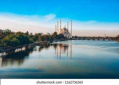 Sabanci Central Mosque in Adana with Seyhan River and Trees. Mosque has reflections from Seyhan river in sunny day with blue clean sky