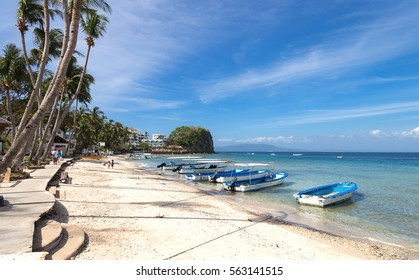 Sabang, Philippines - January 13, 2017: Seascape of beach with transparent sea, blue sky, palms and boats.Taken Sabang, popular tourist and diving spot.