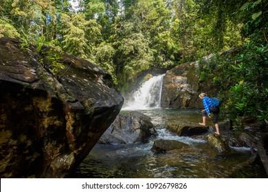 SABARAGAMUWA, SRI LANKA - APRIL 30, 2018: Unidentified girl near the waterfall in the Sinharaja Forest Reserve,  a national park in Sri Lanka. UNESCO World Heritage