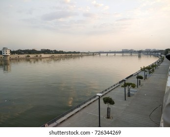 Sabarmati Riverfront, Ahmedabad, Gujarat, India - People walk on pathway near the river. This place is calm and composed and is the heart of the city. Ahmedabad is the World heritage city as well.