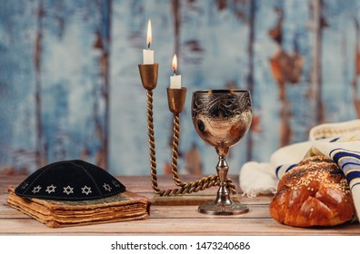 Sabbath challah bread, wine and candelas on wooden table.