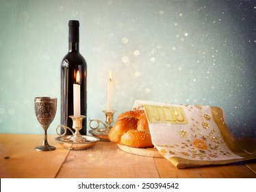 Sabbath image. challah bread, sabbath wine and candelas on wooden table. glitter overlay