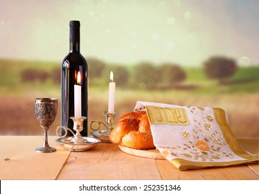 Sabbath image. challah bread, wine and candelas on wooden table.