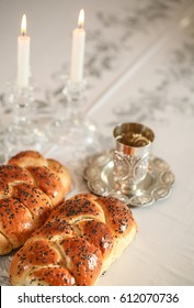 Sabbath image -  Silver kiddush cup, crystal candlesticks with lit candles, and challah challahs
