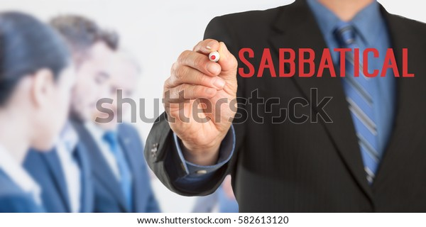 Sabbatical, Male hand in business wear holding a thick pen writing, with office team blurred in background, digital composing.