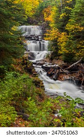 Sable Falls, a waterfall in Upper Peninsula Michigan's Pictured Rocks National Lakeshore, is surrounded by fall color and evergreen trees.