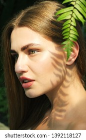 Sable style eyebrows concept. Close up portrait of young sensual model with clean skin, professional make up and beautiful green eyes, laminated eyelashes, tropical background with fern leaves.