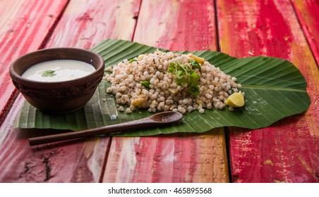 Sabudana Khichadi - An authentic dish from Maharashtra made with sago seeds served over coconut leaf with curd in a wooden bowl