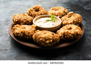 Sabudana vada or Sago fried cake served with peanut chutney over moody background, popular fasting recipe from India.