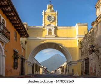 Sacatepequez, Guatemala - July 04, 2019 - Peaceful sunrise at 5th Avenue North in Antigua Guatemala. The Santa Catalina Arch receives the first rays of sunshine, the Agua Volcano in the background.