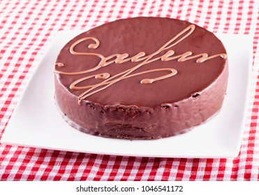 Sacher torte over white and red cloth, horizontal image