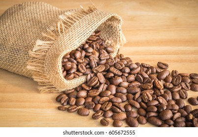 Sack of coffee beans on wooden background