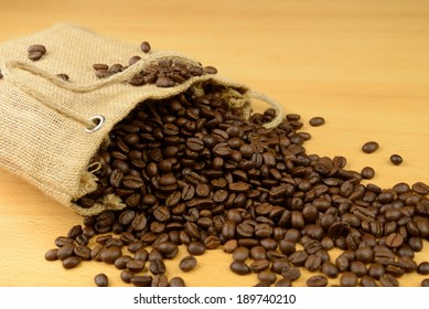 Sack of coffee beans scattered on the table