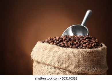 Sack with coffee beans and scoop on brown background