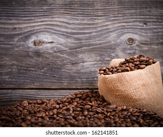 Sack of fresh coffee beans against wooden interior