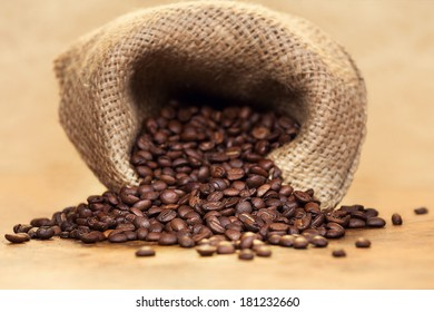 Sack of fresh roasted coffee beans over light background.