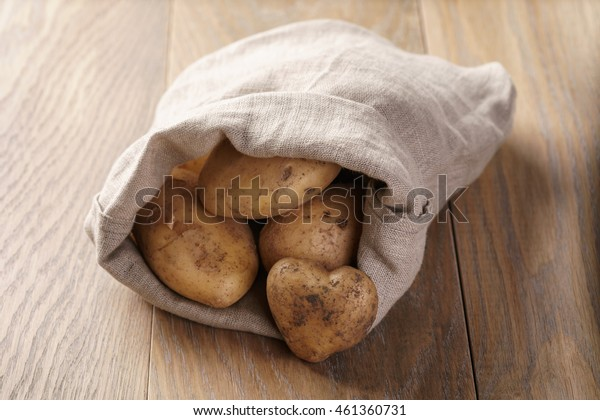 sack full of organic potatoes on oak wooden table
