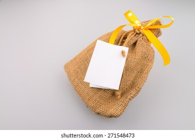 sack gift bag with ribbon bow, and white papers.
