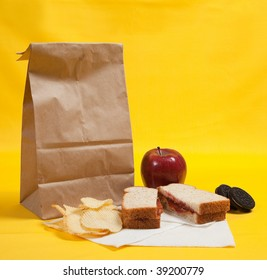 A sack lunch with peanut butter sandwich with apple, chips and cookies