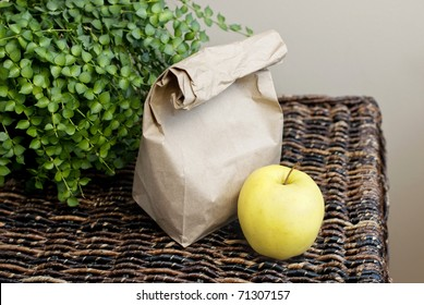 A sack lunch with a yellow apple with focus on apple, horizontal with copy space