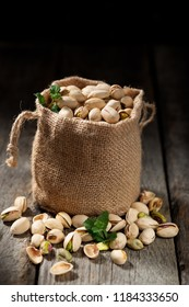 Sack with pistachios on a wooden table.