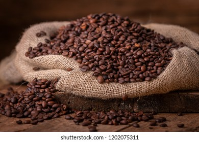 Sack of spilled fresh coffee beans on brown wooden background