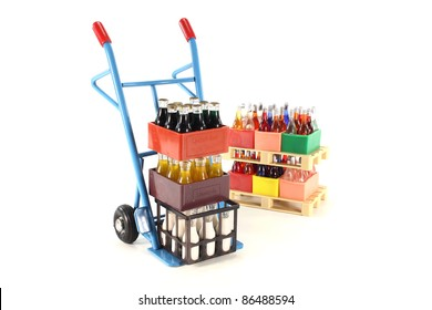 sack truck with cola, lemonade, milk and beverages stacked on euro pallets in the background