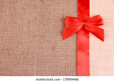 Sackcloth background with color ribbon and bow on wooden board