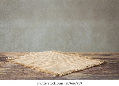 sackcloth on wooden table over wall grunge background, rustic style