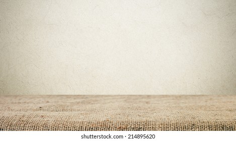 Sackcloth over table and grunge cement  wall, vintage, background, template, display