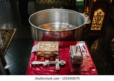 The sacrament of baptism. Attributes of an Orthodox priest for baptism. Baptism in the font. Child and God. Christening candle. Holy water.