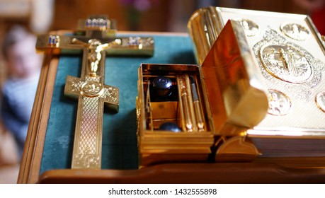 The sacrament of baptism. Attributes of an Orthodox priest for baptism. Baptism in the font. Cross and Bible in a gold.