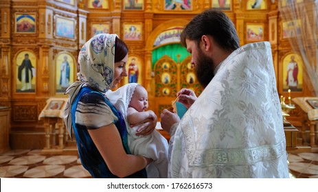 The sacrament of baptism. Priest holding ceremony of orthodoxal Christening the baby in chirch. Child priest and godmother