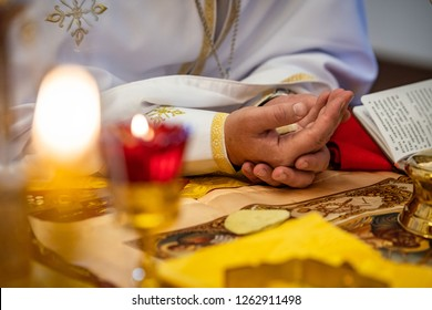 sacrament of communion, bread in the hands of a priest, the priest says a prayer