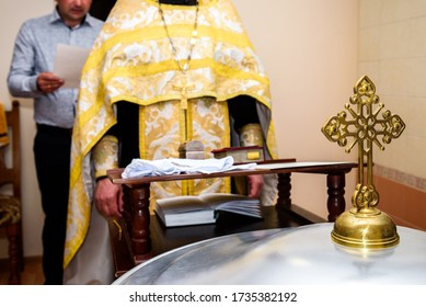 The sacrament of the rite baptism of a child in an Orthodox Christian church. Chan for ablution and altar with a bible.