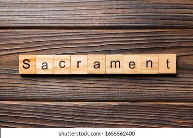 sacrament word written on wood block. sacrament text on table, concept.