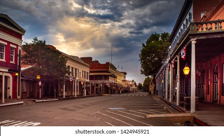 Sacramento, CA—June 11, 2019; sunrise glows on clouds over historic old town Sacramento with two story pioneer and Wild West era wooden saloons, restaurants and other buildings lining streets