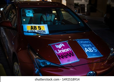 Sacramento, CA—Aug 29, 2019; red care with Uber and Lyft signs displaying fliers advocating for legislative members to vote yes on Assembly Bill, AB 5, to unionize the gig economy