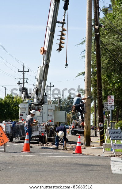 SACRAMENTO - AUGUST 29: Unidentified (SMUD) technicians clean up around a power pole and fix it after car accident on College Oak Ave at the American River College parking entrance, on August 29, 2011 in Sacramento, CA