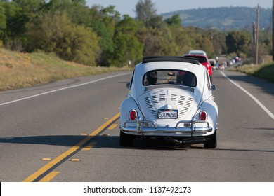 Sacramento, CA - April 5, 2009: Classic white VW Beetle driving on two lane road. Volkswagon cars participating in VW Ranch Run. Second annual event for German car enthusiasts.