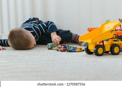 Sacramento, CA - December 29, 2018: Three year old boy playing with HotWheels and other toy cars at home, laying down on carpet in the room.