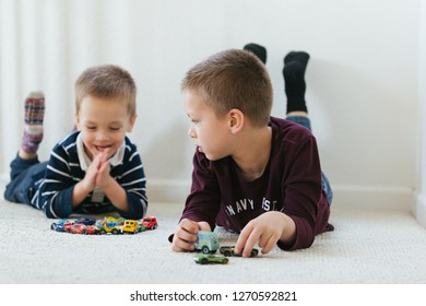 Sacramento, CA - December 29, 2018: Brother boys playing with hot wheels and other cars inside their room, laying on carpet. Hotwheels is world most popular die cast car maker.