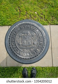 Sacramento, CA - March 24, 2019: State of California seal on a slim piece of concrete, in the park. Mans' shoes visible on bottom.