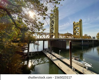 Sacramento, CA - Novmber 16, 2019: View of Tower bridge looking towards the sun during the day in Old Sacramento.