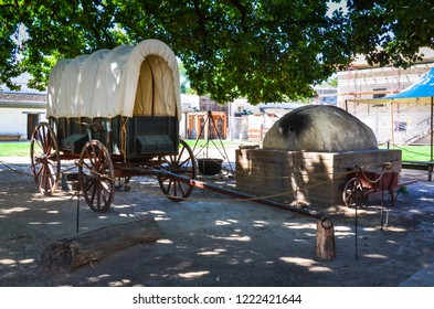 Sacramento, CA / USA - 08-13-2013: Covered wagon and beehive oven in outdoor exhibit at Sutter's Fort in the California State Park system.