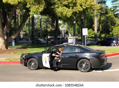 SACRAMENTO, CA, USA - MAY 3, 2018: Cop walking back into police car near the capital building