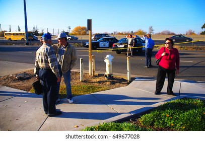 SACRAMENTO, CALIFORNIA, USA - December 2, 2009: People hang around crime scene tape discussing what they know about an armed standoff with California Highway Patrol in the background